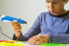 Criança focalizada que cria com a pena da impressão 3d Fotografia de Stock Royalty Free