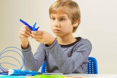 Criança focalizada que cria com a pena da impressão 3d Imagens de Stock