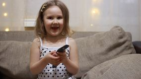 A criança gerencie sobre a tevê usando o telecontrole Televis?o de observa??o do beb? video estoque