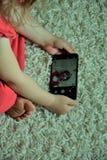 A criança grava-se no smarthone Fotos de Stock