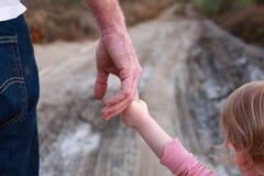 A criança guarda o dedo do paizinho imagens de stock