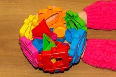 A criança guarda os brinquedos dos blocos de apartamentos em suas mãos e faz a cama Os blocos de apartamentos brincam para crianç Imagem de Stock
