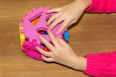 A criança guarda os brinquedos dos blocos de apartamentos em suas mãos e faz a cama Os blocos de apartamentos brincam para crianç Fotografia de Stock