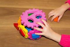 A criança guarda os brinquedos dos blocos de apartamentos em suas mãos e faz a cama Os blocos de apartamentos brincam para crianç Fotos de Stock