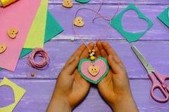 A criança guarda um pendente dado forma coração em suas mãos A criança fez um pendente dado forma coração do feltro, dos grânulos foto de stock royalty free