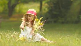 A criança guarda um ramalhete dos wildflowers em suas mãos, cheira-as e sorri-a vídeos de arquivo