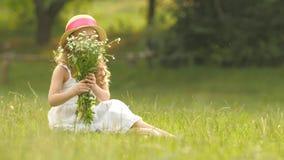 A criança guarda um ramalhete dos wildflowers em suas mãos, cheira-as e sorri-a filme
