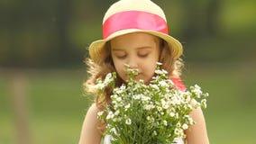 A criança guarda um ramalhete dos wildflowers em suas mãos, cheira-as e sorri-a Movimento lento filme