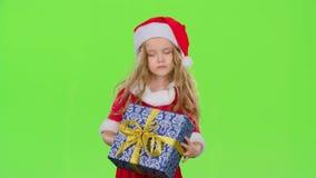 A criança guarda uma caixa de presente em suas mãos e não sabe que ` s para dentro Tela verde Movimento lento vídeos de arquivo