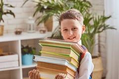 A criança guarda uma pilha de livros de texto fotografia de stock royalty free