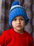 Criança indiana bonito que golpeia uma pose no desgaste do inverno com um sorriso bonito Imagens de Stock Royalty Free