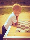 Criança inteligente do rapaz pequeno que joga verificadores no parque Imagens de Stock