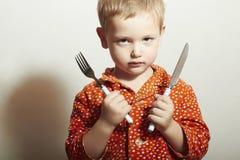 Criança irritada rapaz pequeno com fome com forquilha e faca Alimento Queira comer imagem de stock royalty free