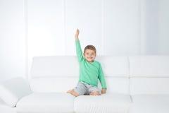 Criança isolada no sofá branco Fotos de Stock Royalty Free