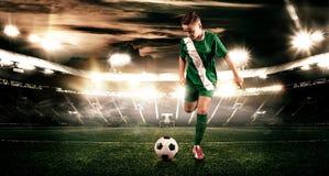 Criança - jogador de futebol Menino para a frente no sportswear do futebol no estádio com bola Conceito do esporte Fotos de Stock Royalty Free