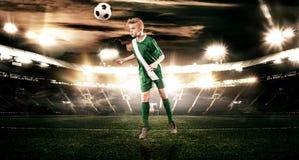 Criança - jogador de futebol Menino para a frente no sportswear do futebol no estádio com bola Conceito do esporte Fotografia de Stock