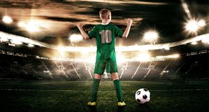 Criança - jogador de futebol Menino para a frente no sportswear do futebol no estádio com bola Conceito do esporte Imagens de Stock