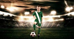 Criança - jogador de futebol Menino para a frente no sportswear do futebol no estádio com bola Conceito do esporte Imagem de Stock