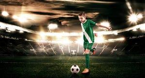 Criança - jogador de futebol Menino para a frente no sportswear do futebol no estádio com bola Conceito do esporte Imagens de Stock Royalty Free