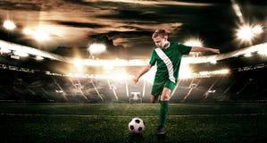 Criança - jogador de futebol Menino para a frente no sportswear do futebol no estádio com bola Conceito do esporte Fotos de Stock
