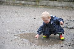 Criança, jogando em uma poça imagem de stock royalty free