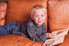 A criança lê dentro um livro fotografia de stock royalty free