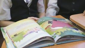 A criança lê o livro no jardim de infância dentro vídeos de arquivo