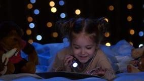 A criança lê um livro nas mãos de um fanático na noite e ri Fundo de Bokeh video estoque