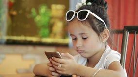 Criança latina moreno da menina que senta-se no café, jogando no smartphone no jogo, indignante, infeliz vídeos de arquivo
