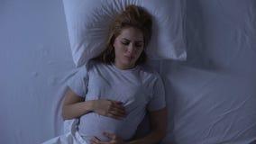 Criança levando da mulher cansado que gerencie na cama, dificuldades da gravidez, pesadelo video estoque