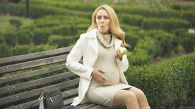 Criança levando fêmea bonita que come a maçã verde, sentando-se no banco de parque, vitaminas video estoque