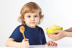 A criança loura bonita está indo comer o cereal do painço do pequeno almoço Fotografia de Stock