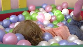 Criança loura bonito caucasiano feliz que tem o divertimento e que joga na multi associação colorida da bola no campo de jogos in vídeos de arquivo
