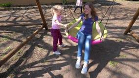 Criança loura bonito da menina para balançar sua mamã no balanço exterior redondo Movimento da suspensão Cardan vídeos de arquivo