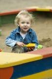 Criança loura bonito que joga na caixa de areia fotografia de stock