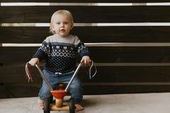 A criança loura pequena bonito adorável preciosa do menino da criança do bebê que joga fora em Toy Bicycle Scooter Mobile Smiling foto de stock