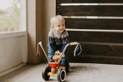 A criança loura pequena bonito adorável preciosa do menino da criança do bebê que joga fora em Toy Bicycle Scooter Mobile Smiling foto de stock royalty free