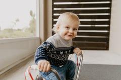 A criança loura pequena bonito adorável preciosa do menino da criança do bebê que joga fora em Toy Bicycle Scooter Mobile Smiling fotografia de stock royalty free
