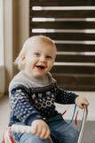 A criança loura pequena bonito adorável preciosa do menino da criança do bebê que joga fora em Toy Bicycle Scooter Mobile Smiling fotos de stock