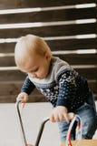 A criança loura pequena bonito adorável preciosa do menino da criança do bebê que joga fora em Toy Bicycle Scooter Mobile Smiling fotos de stock royalty free