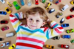Criança loura pequena que joga com lotes de carros do brinquedo Foto de Stock Royalty Free