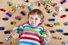 Criança loura pequena que joga com lotes de carros do brinquedo Fotos de Stock
