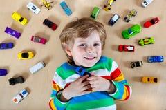 Criança loura pequena que joga com lotes de carros do brinquedo Imagens de Stock Royalty Free