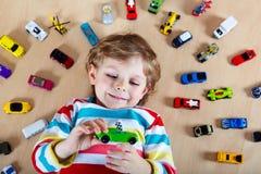 Criança loura pequena que joga com lotes de carros do brinquedo Imagem de Stock