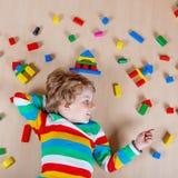 Criança loura pequena que joga com os blocos de madeira coloridos internos Fotos de Stock Royalty Free