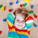 Criança loura pequena que joga com os blocos de madeira coloridos internos Foto de Stock