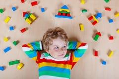 Criança loura pequena que joga com os blocos de madeira coloridos internos Imagens de Stock Royalty Free