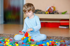Criança loura pequena que joga com os blocos de madeira coloridos internos Foto de Stock Royalty Free