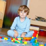 Criança loura pequena que joga com os blocos de madeira coloridos internos Imagem de Stock Royalty Free