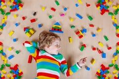 Criança loura pequena que joga com os blocos de madeira coloridos internos Imagem de Stock